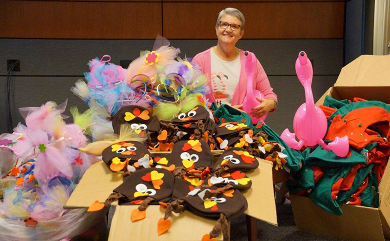 FNB employee Cheryl Stevens with hats that she and fellow employees made.