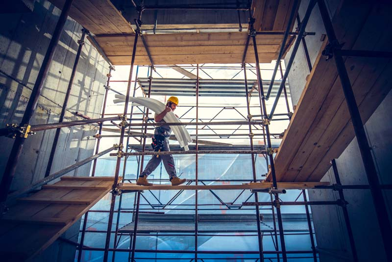 A construction worker walking on scaffolding