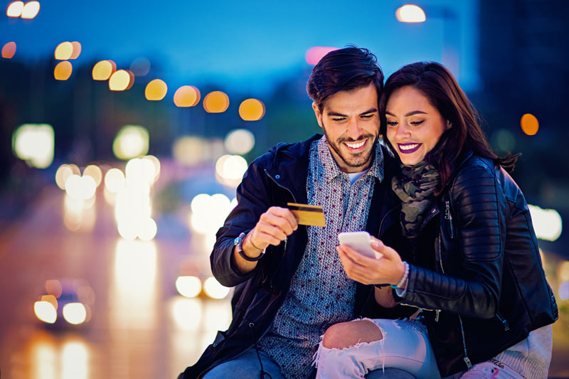 Couple on a date looking at their Samsung phone and smiling