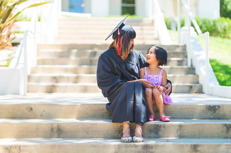Graduate in her gown with her young daughter