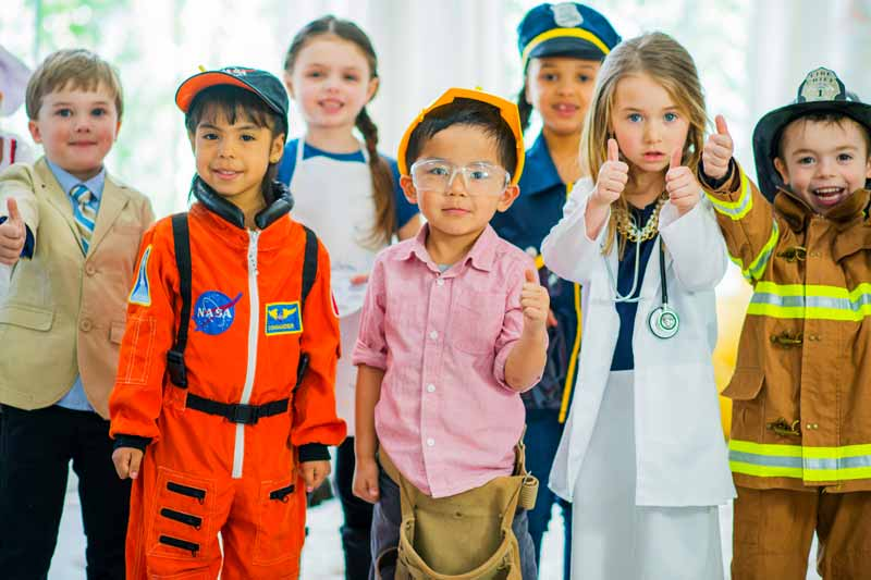 A group of young children playing career day dress up