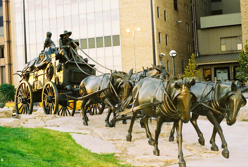 A horse drawn carriage bronze statue
