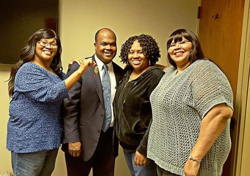 Omaha 100 Program Director, Jerry Dantzler, stands by three sisters and proud new homeowners who recently purchased homes through Omaha 100