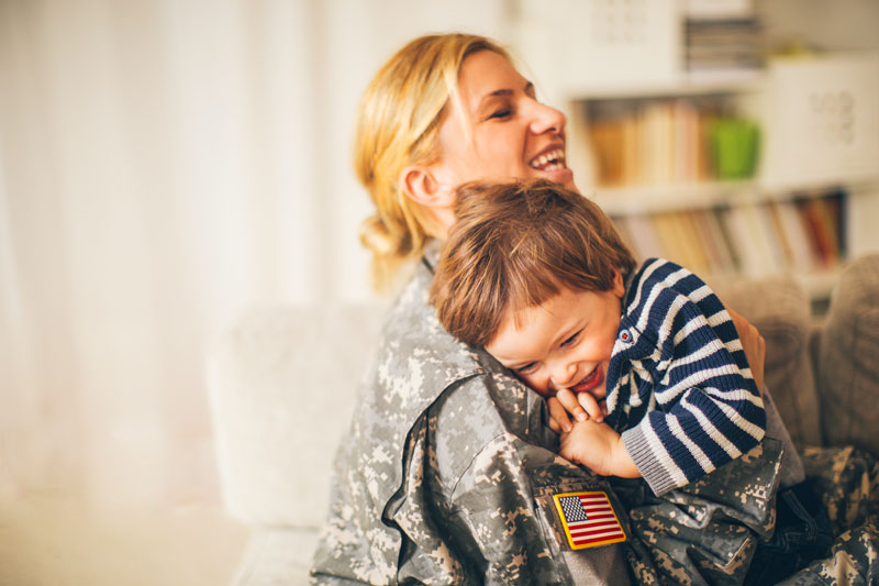 Military mom hugging her son