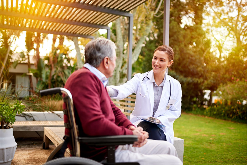 Older man in a wheelchair talking with his nurse outside on a patio
