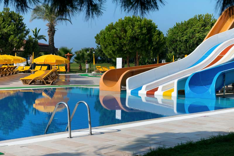 An outside pool with slides, yellow chairs and yellow umbrellas
