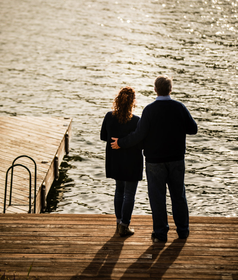 A couple staring at a lake from a dock